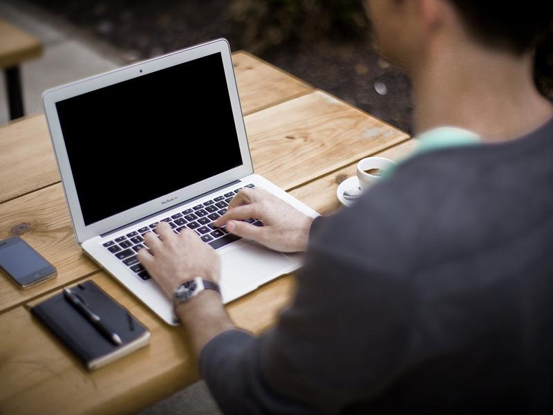Un hombre escribe en su laptop